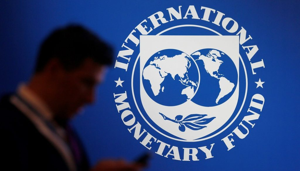 A participant stands near a logo of IMF at the International Monetary Fund - World Bank Annual Meeting 2018 in Nusa Dua